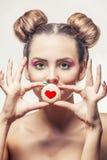 Muchacha hermosa del modelo de moda con las galletas dulces con los corazones en a Imagenes de archivo