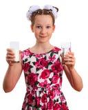 Muchacha hermosa del niño que sostiene los vidrios de leche y de agua clara Imágenes de archivo libres de regalías
