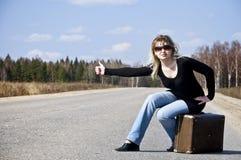 Muchacha hermosa del país que hace autostop en el camino Imágenes de archivo libres de regalías