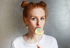 Muchacha hermosa del pelirrojo con el caramelo redondo multicolor y peinado divertido en el fondo de plata Foto de archivo libre de regalías
