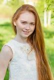 Muchacha hermosa del pelirrojo con el pelo largo en un parque con los dientes de león Fotografía de archivo libre de regalías