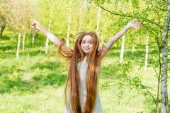 Muchacha hermosa del pelirrojo con el pelo largo en un parque con los dientes de león Imagenes de archivo