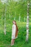 Muchacha hermosa del pelirrojo con el pelo largo en un parque con los dientes de león Fotos de archivo
