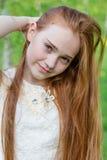 Muchacha hermosa del pelirrojo con el pelo largo en un parque con los dientes de león Imagen de archivo libre de regalías