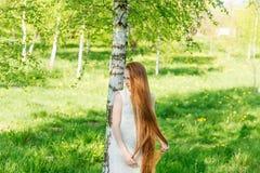 Muchacha hermosa del pelirrojo con el pelo largo en un parque con los dientes de león Imágenes de archivo libres de regalías