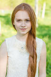 Muchacha hermosa del pelirrojo con el pelo largo en un parque con los dientes de león Foto de archivo libre de regalías