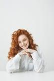 Muchacha hermosa del pelirrojo con el pelo rizado que sonríe mirando la cámara que se sienta en la tabla sobre el fondo blanco Foto de archivo libre de regalías