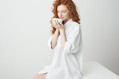 Muchacha hermosa del pelirrojo con el pelo rizado que sonríe sosteniendo la taza que se sienta en la tabla sobre el fondo blanco  Fotos de archivo libres de regalías