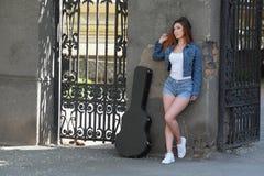 Muchacha hermosa del pelirrojo en la calle con una guitarra en el caso Foto de archivo libre de regalías
