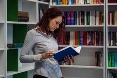 Muchacha hermosa del pelirrojo que estudia en la biblioteca Lectura de un libro w Imágenes de archivo libres de regalías