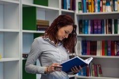 Muchacha hermosa del pelirrojo que estudia en la biblioteca Lectura de un libro w Fotografía de archivo