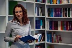 Muchacha hermosa del pelirrojo que estudia en la biblioteca Lectura de un libro w Foto de archivo libre de regalías