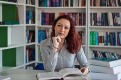 Muchacha hermosa del pelirrojo que piensa con una pila de libros al lado de ella Fotos de archivo libres de regalías