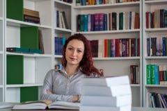 Muchacha hermosa del pelirrojo que se sienta y que piensa con los libros alrededor de los wi Fotografía de archivo libre de regalías
