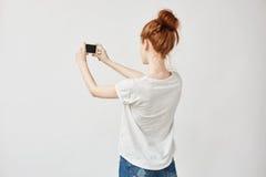 Muchacha hermosa del pelirrojo que sostiene el teléfono que se coloca de nuevo a cámara Imagen de archivo