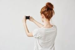 Muchacha hermosa del pelirrojo que sostiene el teléfono que se coloca de nuevo a cámara Fotos de archivo libres de regalías