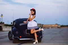 Muchacha hermosa del perno-para arriba que presenta con el coche caliente del camino Foto de archivo