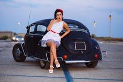 Muchacha hermosa del perno-para arriba que presenta con el coche caliente del camino Fotografía de archivo