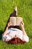 Muchacha hermosa del Redhead que lee un libro en naturaleza imagen de archivo libre de regalías