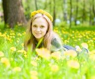 Muchacha hermosa del retrato con una guirnalda de los dientes de león que mienten en la hierba Imagenes de archivo
