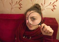 Muchacha hermosa del tennager que mira a través de una lupa Foto de archivo libre de regalías