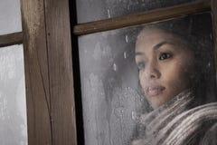 Muchacha hermosa detrás de la ventana Imagen de archivo libre de regalías