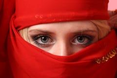 Muchacha hermosa detrás de una bufanda roja Fotografía de archivo