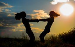 Muchacha hermosa dos que se divierte junto en el tiempo de la puesta del sol Imagen de archivo