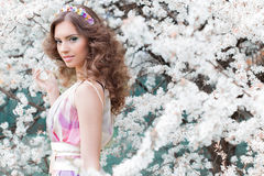 Muchacha hermosa elegante con el pelo enorme con un borde de flores brillantemente coloreadas en un jardín cerca de una mañana ca Imagen de archivo libre de regalías