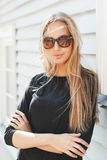 Muchacha hermosa elegante en gafas de sol cerca de una pared de madera Imagen de archivo