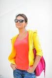 Muchacha hermosa elegante en gafas de sol contra la pared blanca Fotos de archivo