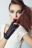 Muchacha hermosa elegante en guantes negros, con maquillaje brillante y pelo, labio rojo Fotos de archivo