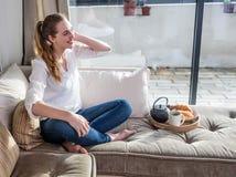 Muchacha hermosa emocionada que goza sentando pies desnudos en el sofá cómodo Foto de archivo libre de regalías