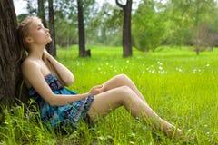 Muchacha hermosa en alineada azul en el prado Imagen de archivo
