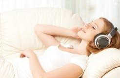 Muchacha hermosa en auriculares que disfruta de música en casa Imagen de archivo
