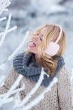 Muchacha hermosa en auriculares rosados en la bufanda con nieve Imagenes de archivo
