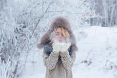 Muchacha hermosa en auriculares rosados en la bufanda con nieve Imagen de archivo libre de regalías