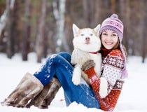 Muchacha hermosa en bosque del invierno con el perro Fotos de archivo libres de regalías