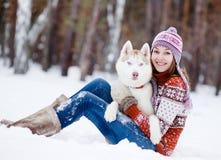 Muchacha hermosa en bosque del invierno con el perro Foto de archivo