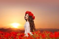 Muchacha hermosa en campo de las amapolas en la puesta del sol Po adolescente sonriente feliz Fotos de archivo libres de regalías