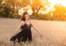 Muchacha hermosa en campo de trigo en la puesta del sol Fotografía de archivo