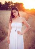Muchacha hermosa en campo de trigo en la puesta del sol Imagenes de archivo