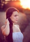 Muchacha hermosa en campo de trigo en la puesta del sol Imagen de archivo libre de regalías