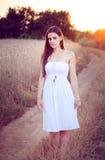 Muchacha hermosa en campo de trigo en la puesta del sol Imagen de archivo