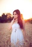 Muchacha hermosa en campo de trigo en la puesta del sol Fotos de archivo libres de regalías