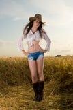 Muchacha hermosa en campo de trigo en puesta del sol Foto de archivo libre de regalías