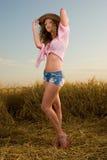 Muchacha hermosa en campo de trigo en puesta del sol Fotografía de archivo