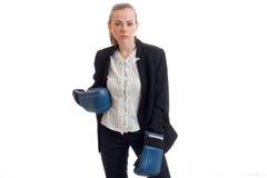 Muchacha hermosa en chaqueta negra del negocio y la camisa blanca que presentan en cámara con los guantes de boxeo a mano Fotos de archivo