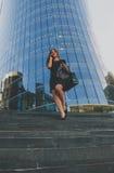 Muchacha hermosa en chaqueta negra en sus manos que vienen abajo los pasos del centro de negocios Imágenes de archivo libres de regalías