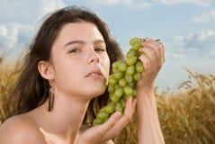 Muchacha hermosa en comida campestre en campo con las uvas Imagen de archivo libre de regalías